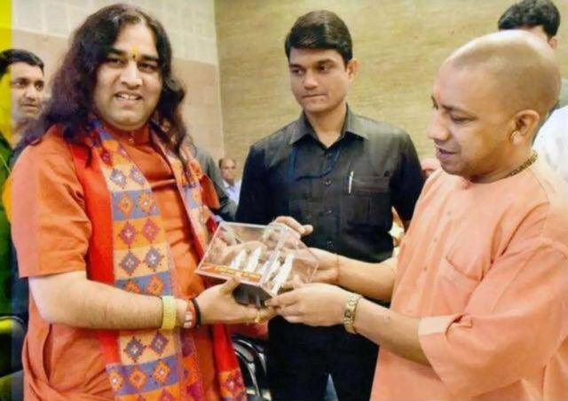 Devkinandan Thakur receiving award from Yogi Adityanath