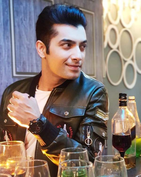 Sharad Malhotra sitting with a bottle of wine