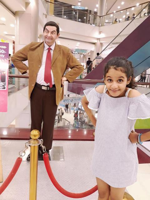 Syna Anand posing with Mr. Bean's statue