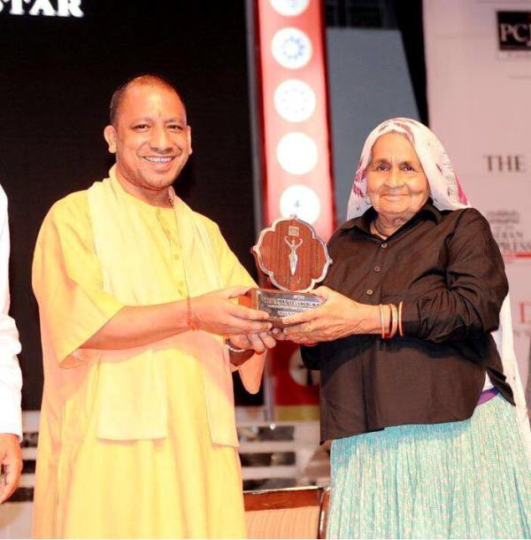 Chandro Tomar receiving Devi Award from CM Adityanath Yogi