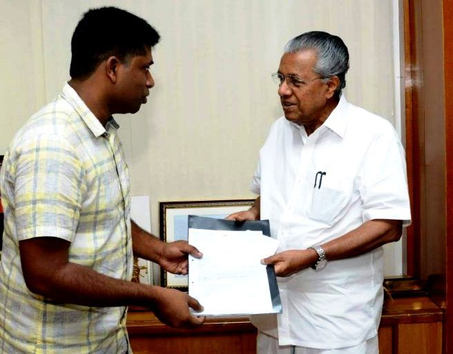 Kannan Gopinathan presenting a cheque of 1 Crores towards the Kerala CM Disaster Relief Fund