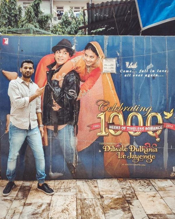 Soham Shah posing in front of the poster of DDLJ