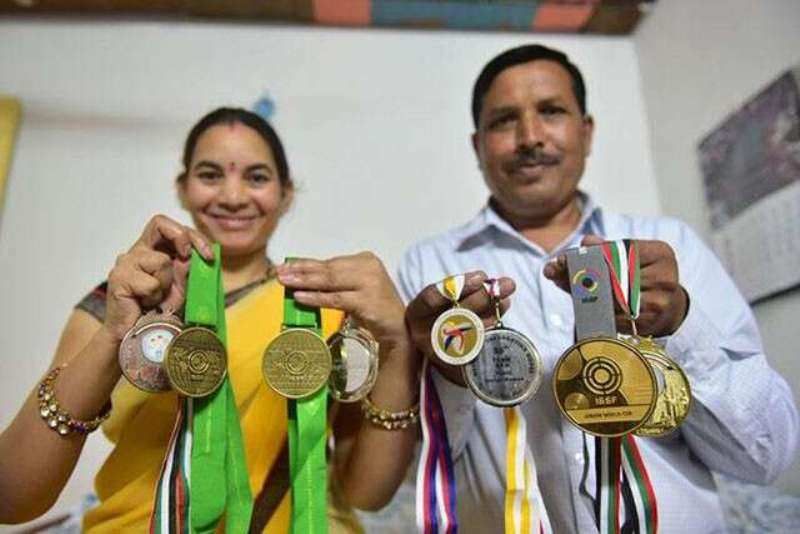 Parents of Chinki Yadav showing the medals won by Chinki