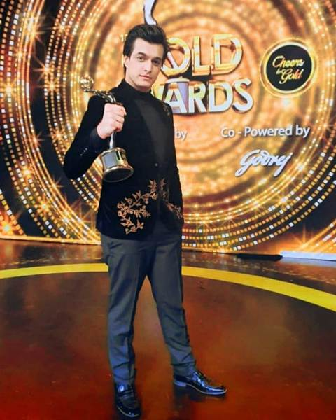 Mohsin Khan posing with an award