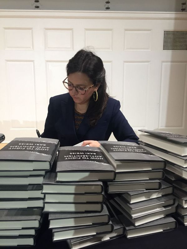 Bari Weiss with a pile of her book, How to Fight Anti-Semitism