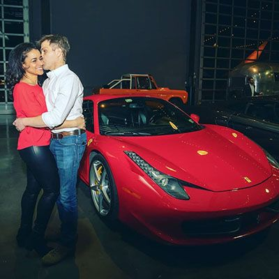 Sara Cooper and Her Husband Posing in Front of her Car