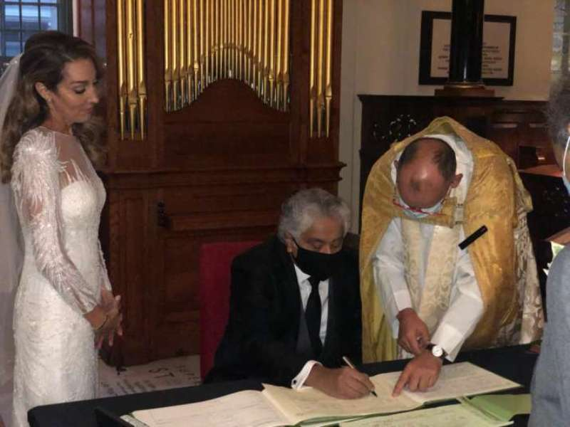 Caroline Brossard and Harish Salve entering their names in the marriage register of a church in London