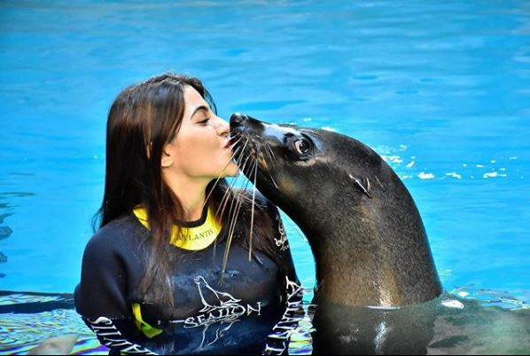 Nikki Tamboli kissing a sea lion