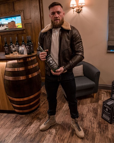 Conor McGregor with a bottle of his brand, Proper No. Twelve's whiskey bottle