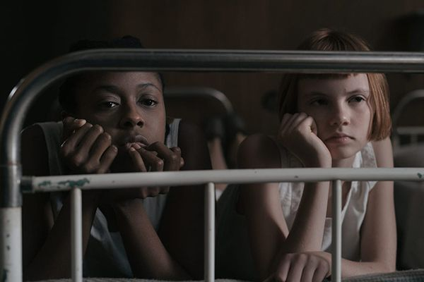 Beth Harmon (played by Isla Johnston) with Jolene (Moses Ingram) in a scene from The Queen's Gambit (2020)