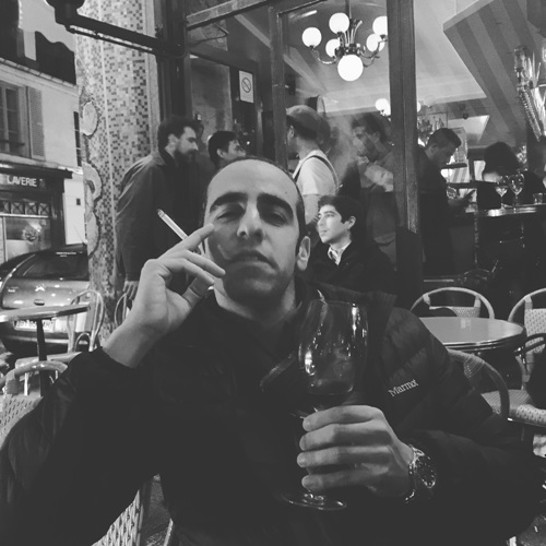 Dan Ahdoot enjoying wine and a cigarette at a restaurant