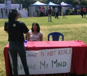 Disha Ravi sitting on a bench challenging people to debate on global climate change issue