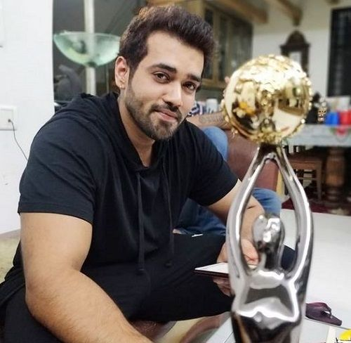 Karan Khanna posing with his award