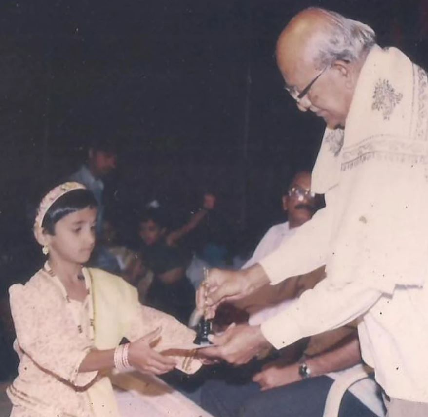 An old photo of preteen Divya Uruduga receiving an award for her performance at school annual function