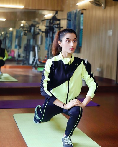 Arushi Nishank performing stretching exercise in the gym