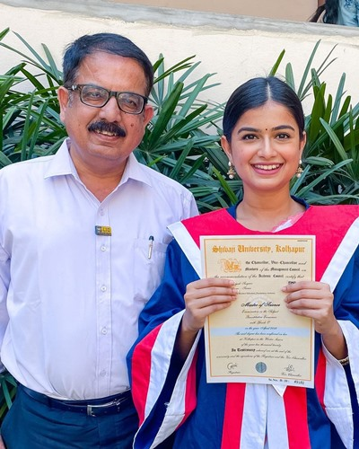 Hemal Ingle holding her master's degree with her father