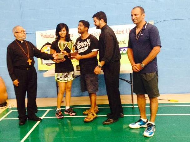 Michelle Ann Daniel receiving a trophy for winning a badminton competition in her school