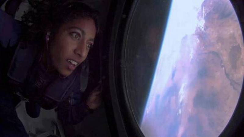 Sirisha Bandla looks out the window at Earth in zero gravity on board Virgin Galactic's passenger rocket plane VSS Unity after reaching the edge of space on July 11, 2021