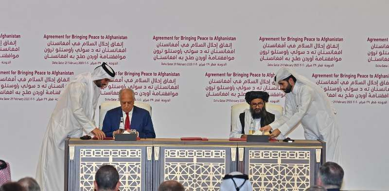 US representative Zalmay Khalilzad (left) and Baradar (right) sign the Agreement for Bringing Peace to Afghanistan in Doha, Qatar, on 29 February 2020