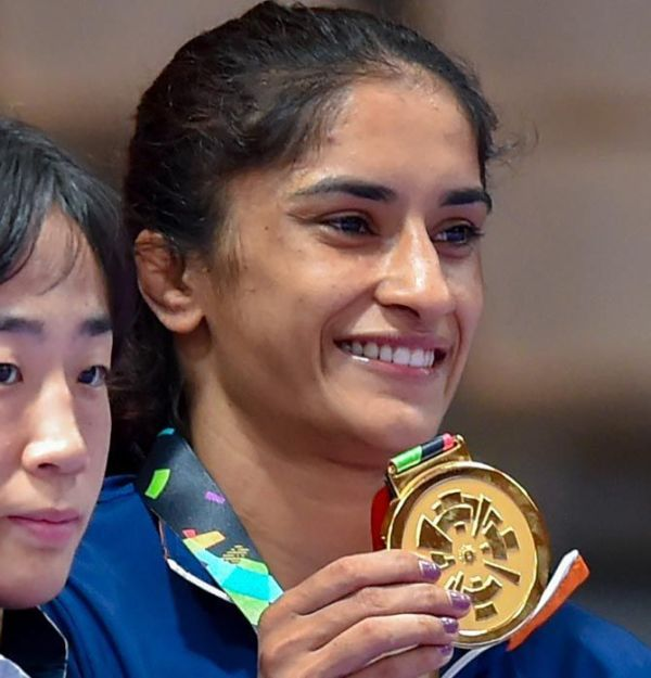 Vinesh Phogat shows off her gold medal from the podium after the medal ceremony for the 50 kg category wrestling competition at the Asian Games 2018