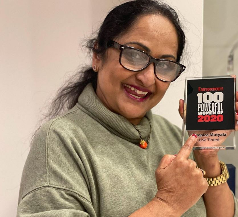 Deepica's mother while posing with Deepica's award
