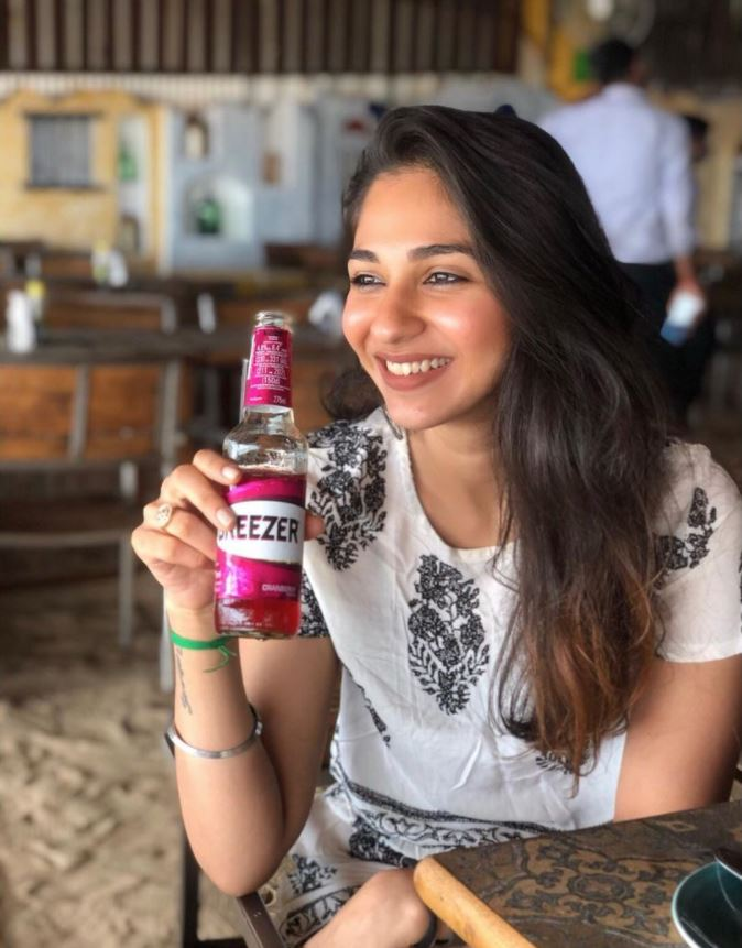 Vidhi Pandya with a bottle of alcohol